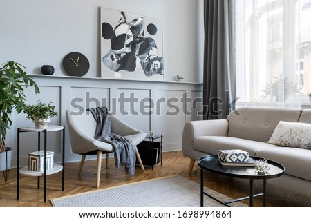 Stylish scandinavian home interior of living room with design gray sofa, armchair, marble stool, black coffee table, modern paintings, decoration, plant and elegant personal accessories in home decor.