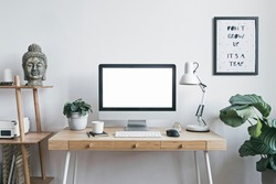 Stylish scandinavian interior of home creative desk with mock up computer screen, plants, bookstand and buddha figure. Minimalistic space for work, hobby and listen music. Freelancer zone.