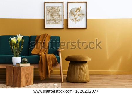 Stylish scandinavian interior of living room with design green velvet sofa, gold pouf, wooden furniture, cacti, carpet, cube, copy space and mock up poster frames. Template.