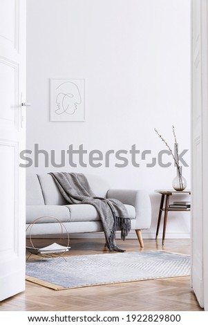 Stylish scandinavian interior of living room with design grey sofa, retro wooden table, mock up poster frame, decoration , carpet and personal accessories in elegant home decor.