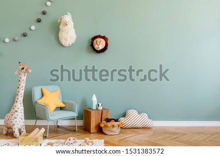 Stylish scandinavian kid room with toys, teddy bear, plush animal toys, mint armchair, umbrella, cotton balls. Modern interior with eucalyptus background walls, Design interior of childroom. Template