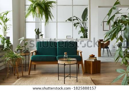 Stylish scandinavian living room interior with green velvet sofa, coffee table, carpet, plants, furniture, elegant accessories in modern home decor. Template.