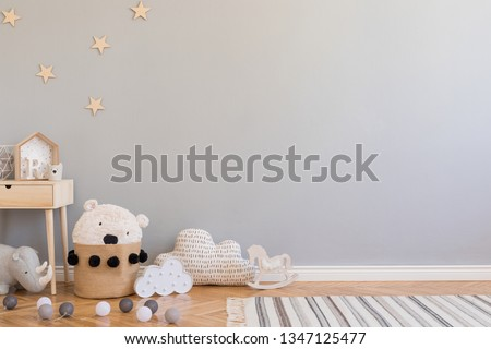 Stylish scandinavian newborn baby room with toys, children's chair, natural basket with teddy bear and small shelf. Modern interior with grey background walls, wooden parquet and stars pattern.