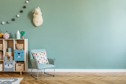 Stylish scandinavian newborn baby room with wooden cabinet, toys, children's armchair and pillow. Modern interior with eucalyptus background walls, wooden parquet and cotton balls. Cute home decor.