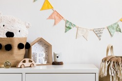 Stylish scandinavian nursery interior with white shelf, teddy bear, wooden toys and house. Hanging cotton flags and natural basket on the white background wall. Cozy and sunny childroom.