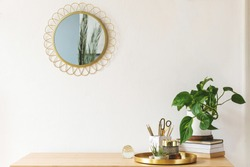 Stylish scanidnavian interior with wooden desk, design gold accessories, books and plants. Beautiful mirror on the white wall. Creative desk of home decor. Warm and sunny room. Copy space. Real photo.