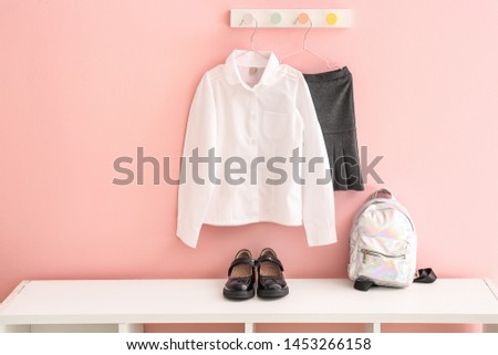 Stylish school uniform with backpack and shoes in room