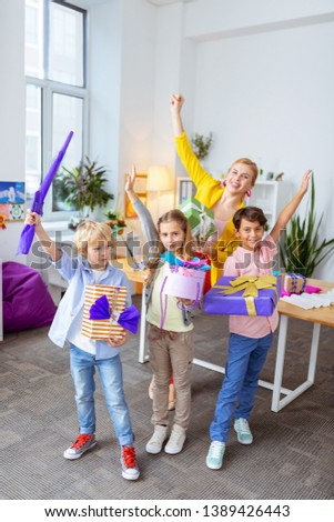 Stylish schoolchildren. Stylish schoolchildren standing near teacher with their present boxes after art lesson