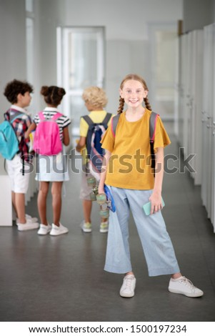 Stylish schoolgirl. Stylish schoolgirl holding penny board and smartphone while standing near lockers