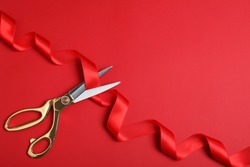 Stylish scissors and red ribbon on color background, flat lay with space for text. Ceremonial tape cutting