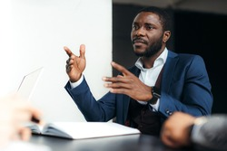 Stylish serious african american man in the office communicates with workers gesturing with his hands
