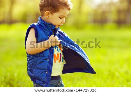 Stylish serious baby boy with ginger (red) hair wearing blue jacket, standing in the park and trying to find something in his pocket. Hipster style. Sunny weather. Copy-space. Outdoor shot