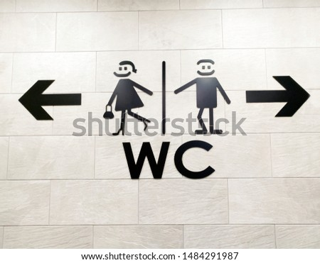Stylish set of toilet icons. Men and women WC signs for restroom with arrows. Restroom sign on a toilet wall. #1484291987