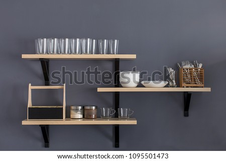 Stylish shelf with various dishware hanging on gray wall.  #1095501473