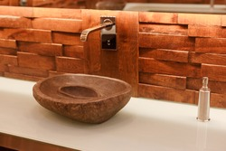 Stylish sink made of light natural stone. Bathroom with stone washbasin on a wooden top in a tropical loft style.