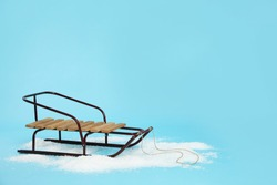 Stylish sleigh in pile of snow on light blue background, space for text