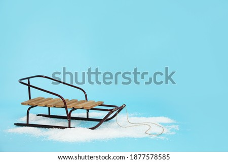 Stylish sleigh in pile of snow on light blue background, space for text ストックフォト ©