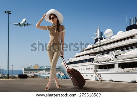 Stylish slim woman wearing sunglasses and white hat standing in seaport near docked cruise ship while smiling and holding her luggage on a summer sunny day. Travel, vacation, adventure concept.