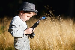 Stylish small boy with retro camera photographing outdoors at sunny autumn day