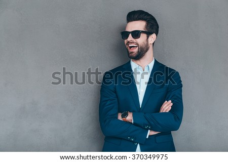 Stylish smile. Cheerful young handsome man in sunglasses keeping arms crossed and looking away with smile while standing against grey background Stock photo ©