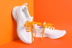 Stylish sneakers with shoe laces on orange background