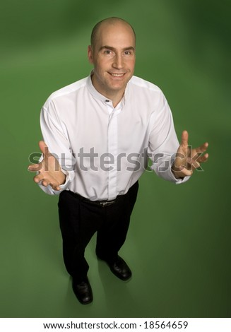 Stylish 30-something man standing smiling at camera with hands raised as if holding something.