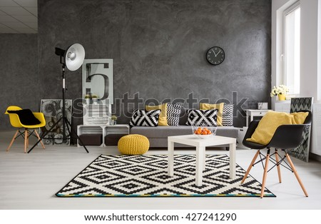 Stylish spacious living room with grey walls and black, white and yellow decorations