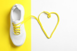 Stylish sportive shoe and yellow laces in shape of heart on color background, flat lay
