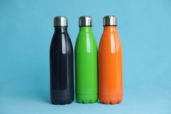 Stylish stainless thermo bottles on light blue background