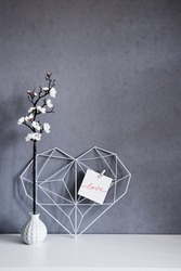 Stylish still life inside the apartment. Elegant openwork heart with notes on the background of a concrete wall in the interior. Minimalism. Concept Symbol of love and Valentine's Day. Home Decor