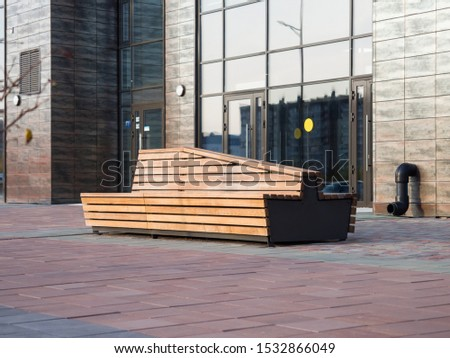 Stylish street bench near the entrance to the office building. Comfortable urban environment