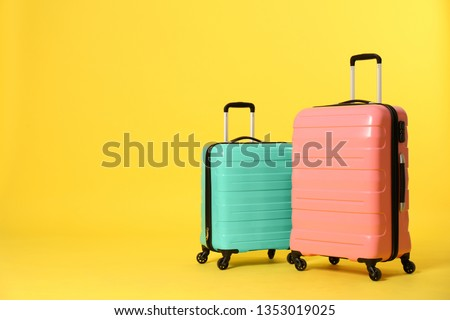 Stylish suitcases on color background. Space for text