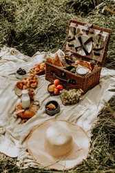 Stylish summer picnic in the park with a basket and food. Fresh pastries with milk and croissants. Fruits and berries in a picnic basket.