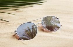 Stylish sunglasses with reflection of palm trees on white sand
