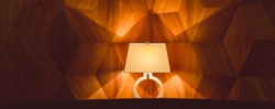 Stylish table lamp shines with warm light at the wooden art Nouveau wall