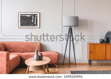 Stylish tall grey lamp in elegant living room interior with comfortable brown corner sofa