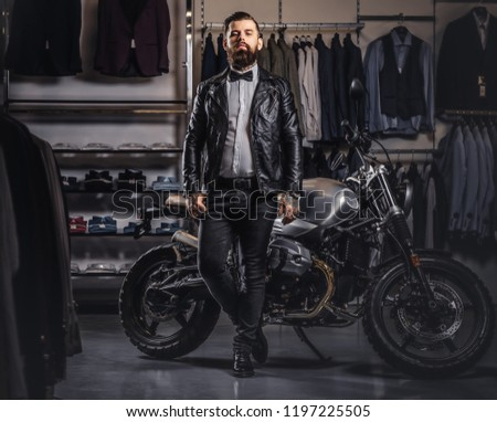 Stylish tattooed bearded man with dressed in black leather jacket and bow tie posing near retro sports motorbike at men's clothing store. #1197225505