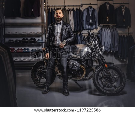 Stylish tattooed bearded man with dressed in black leather jacket and bow tie posing near retro sports motorbike at men's clothing store. #1197225586
