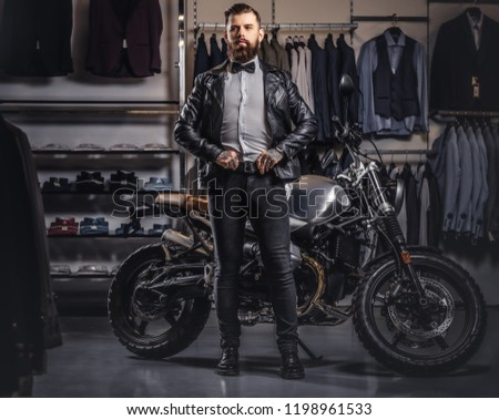 Stylish tattooed bearded man with dressed in black leather jacket and bow tie posing near retro sports motorbike at men's clothing store. #1198961533