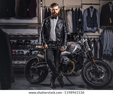 Stylish tattooed bearded man with dressed in black leather jacket and bow tie posing near retro sports motorbike at men's clothing store. #1198961536