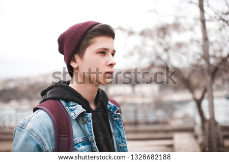 Stylish teen boy 16-17 year old wearing knitted hand and denim jacket outdoors.