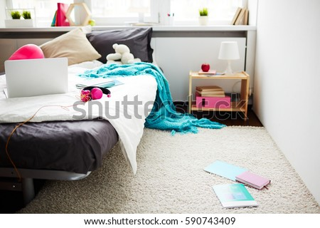 Stylish teen girl messy bedroom with blanket hanging down from bed and books lying on white soft carpet