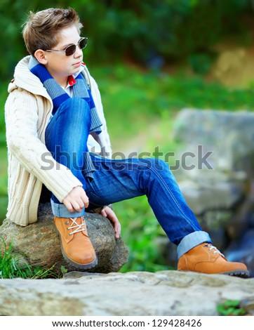 stylish teenage boy sitting on rock outdoors