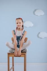 Stylish teenage girl is enjoying her modern kanekalon hair. little girl in fashionable denim overalls.girl sits on a wooden chair in the studio
