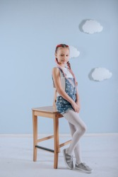 Stylish teenage girl is enjoying her modern kanekalon hairstyle. little girl in fashionable denim overalls.girl sits on a wooden chair in the studio