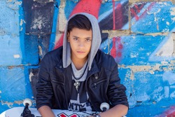 Stylish teenager boy wearing hood shirt with skateboard in city graffiti background looking at you camera sitting