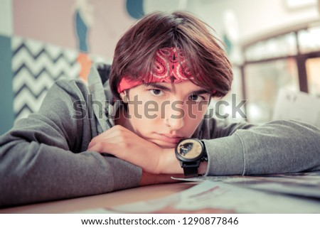 Stylish teenager. Teenager wearing a bandanna and a watch putting his head on hands