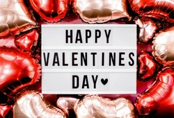 Stylish text frame lightbox with the inscription happy Valentine's day. Pink, red and beige hearts all around. Foil balloons top view of Valentine's Day. Copyspace.