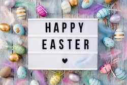 Stylish text frame of the lightbox with the inscription happy easter. Pink, blue, white, gold, and yellow eggs are everywhere. Colorful Easter eggs top view of happy Easter. Copyspace.