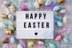 Stylish text frame of the lightbox with the inscription happy easter. Pink, blue, white, gold, and yellow eggs are everywhere. Colorful Easter eggs top view. Copyspace.